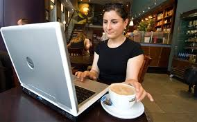 Photo: Woman works on computer at cafe